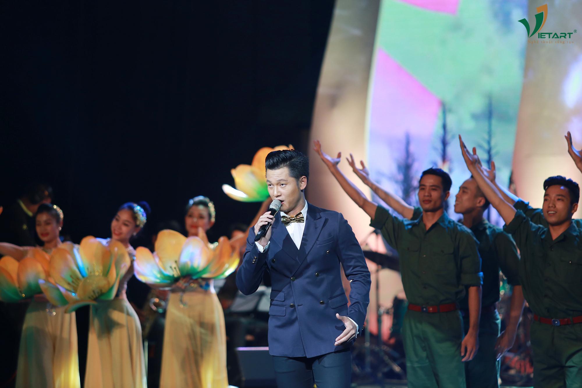 """Ca sĩ Đức Tuấn mở đầu chương trình với hai ca khúc """"Trên đỉnh Trường Sơn ta hát"""" và """"Sẽ về thủ đô"""" của nhạc sĩ Huy Du."""